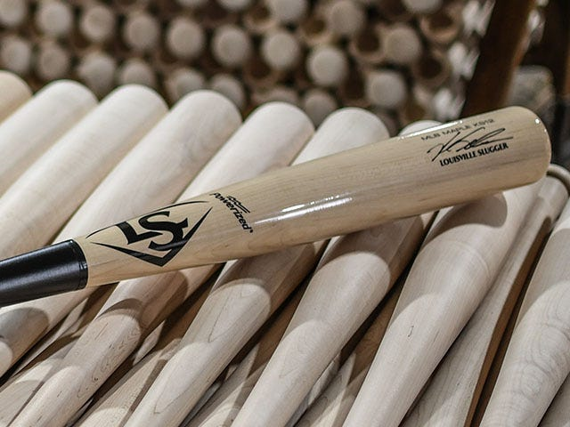KS12 Signature bat laying on top of unfinished baseball bats